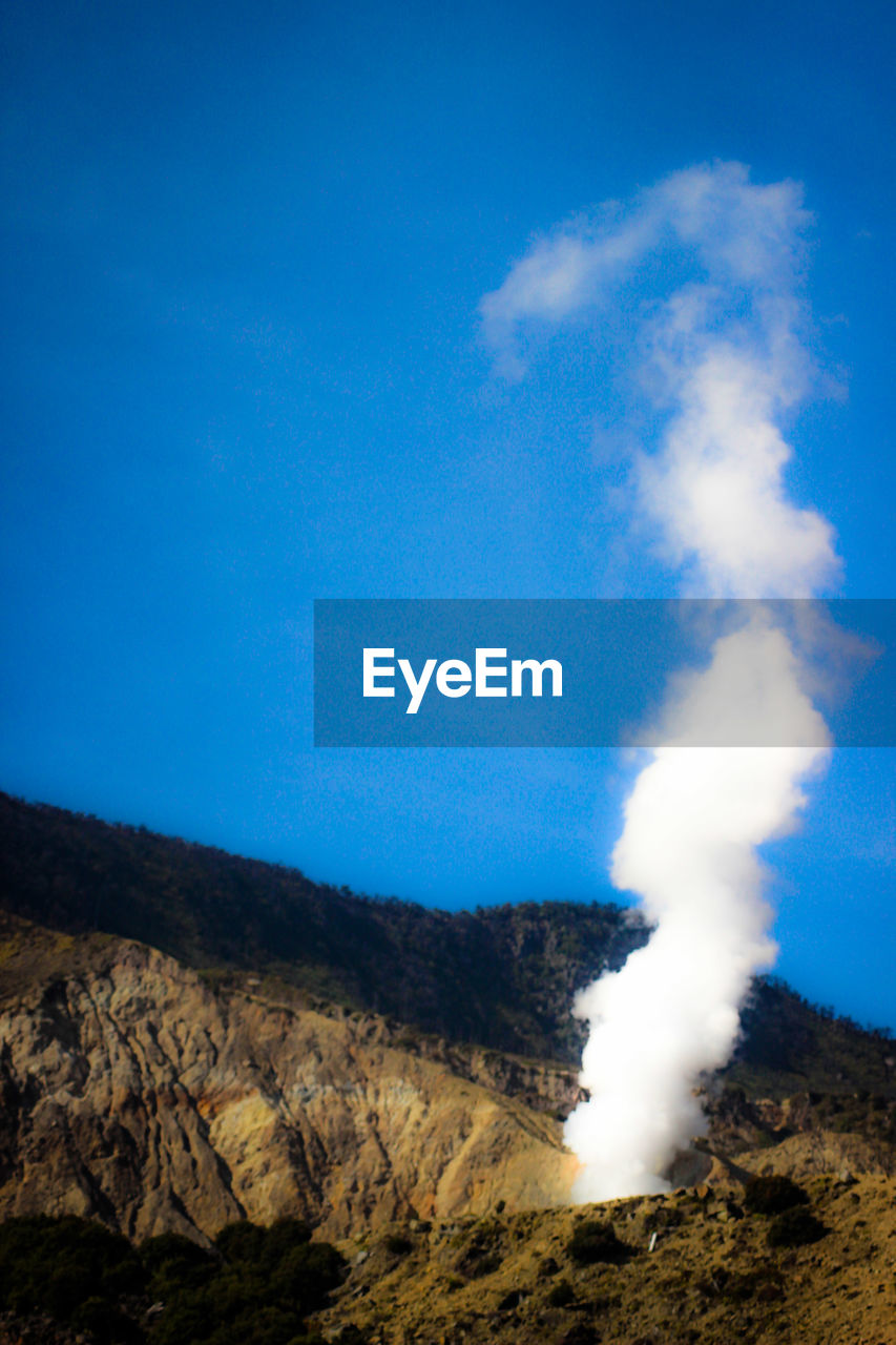 sky, mountain, blue, geology, environment, smoke - physical structure, scenics - nature, nature, physical geography, beauty in nature, erupting, landscape, non-urban scene, volcano, no people, power in nature, land, day, tranquil scene, smoke, outdoors, formation, pollution, volcanic crater