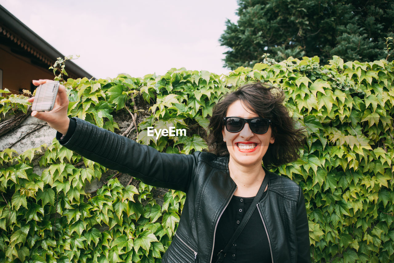 Smiling woman taking selfie with smart phone while standing against plants at park