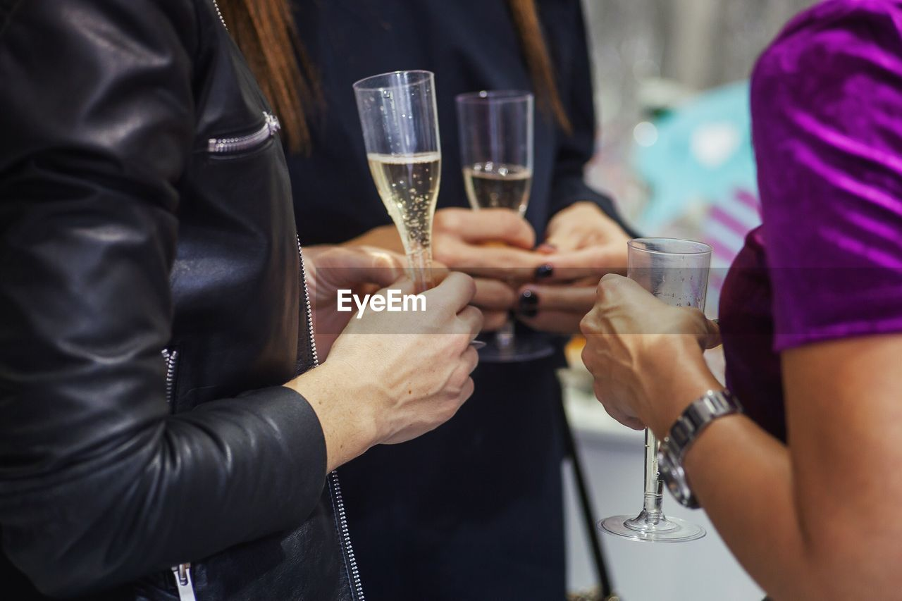 Midsection Of Friends With Champagne In Party