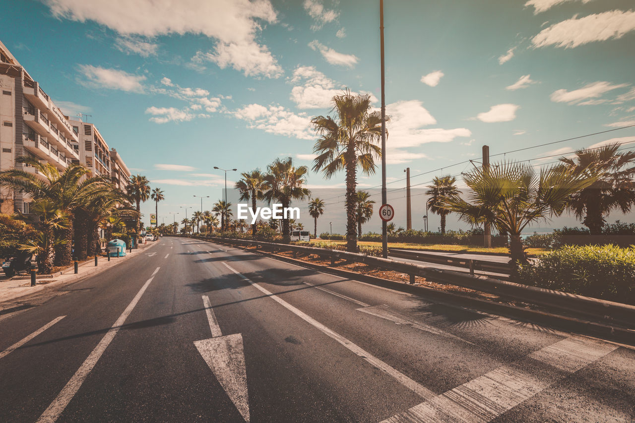 road, transportation, tree, sky, the way forward, palm tree, cloud - sky, outdoors, no people, day, built structure, architecture, nature, city