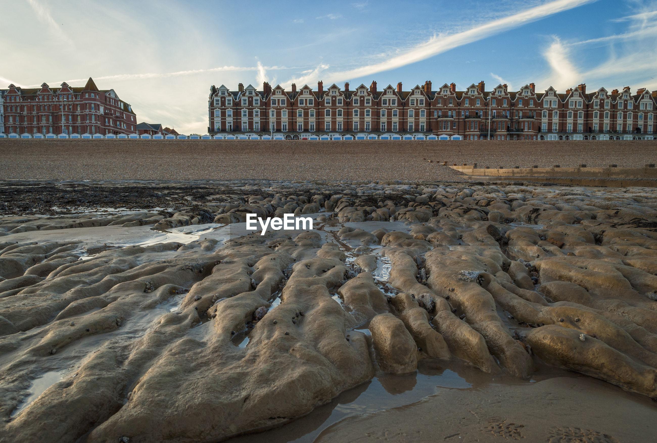 Rocks at shore against buildings in city
