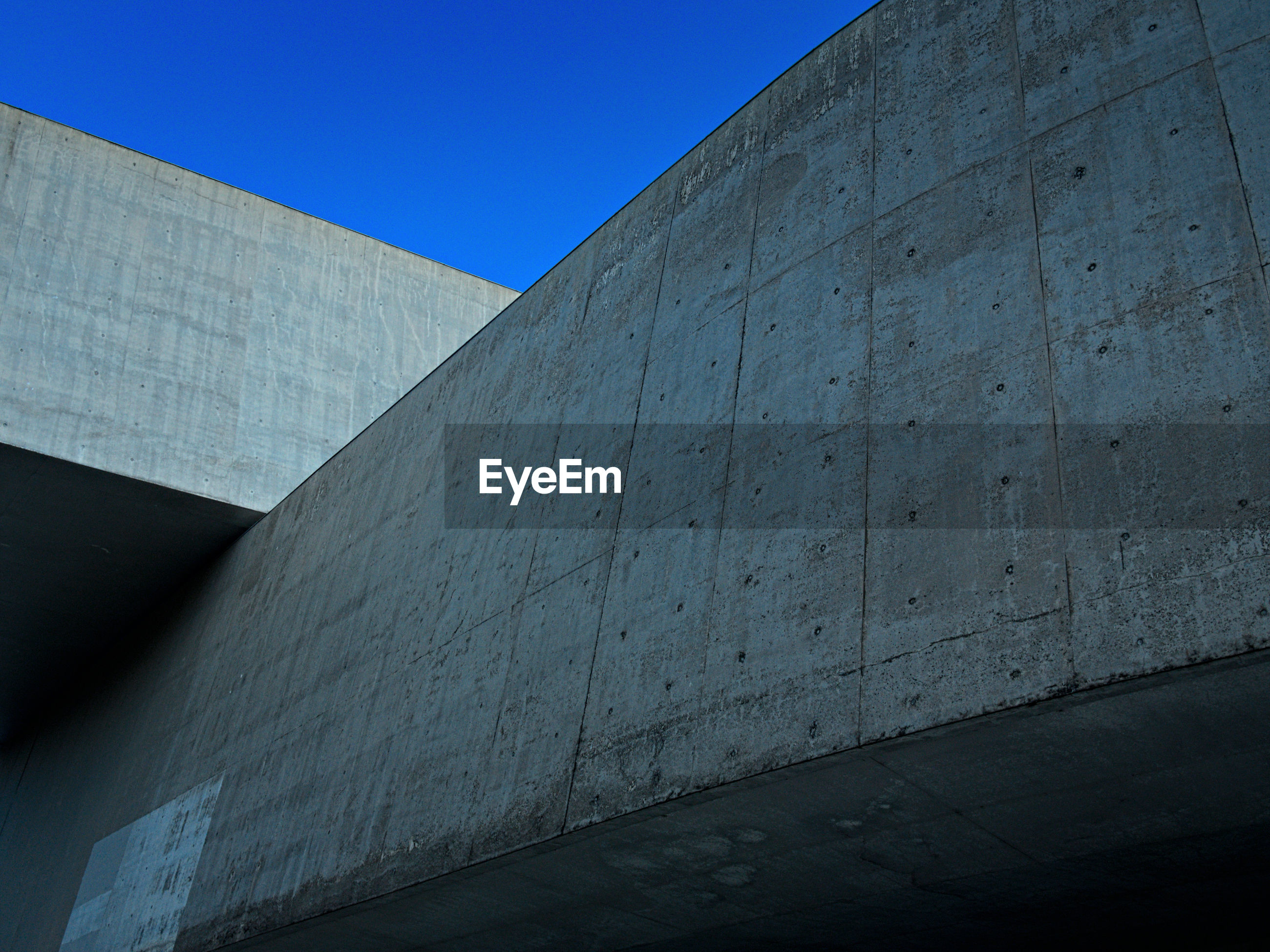 Low angle view of concrete wall against clear blue sky