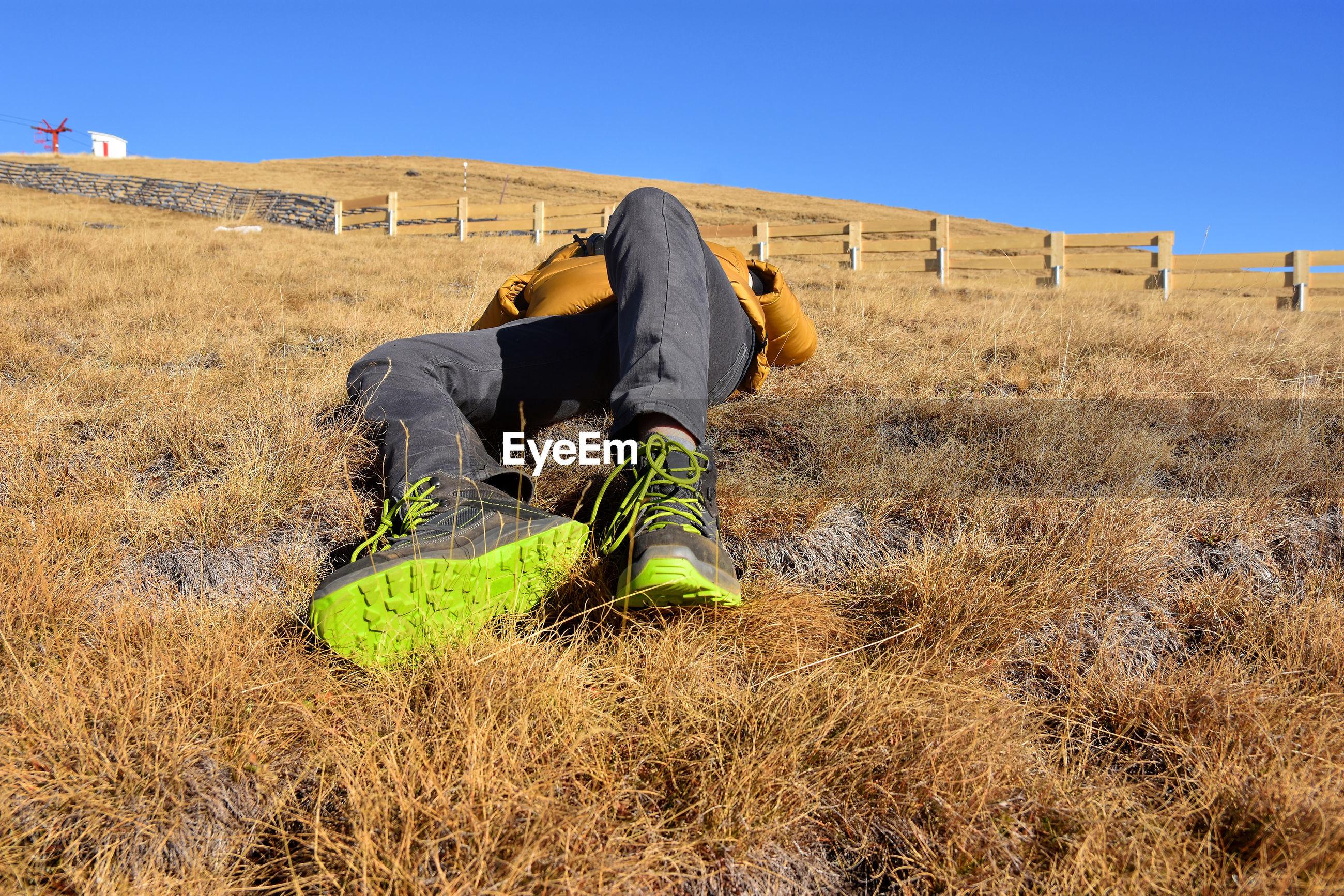 Teenage boy lying on field against clear blue sky