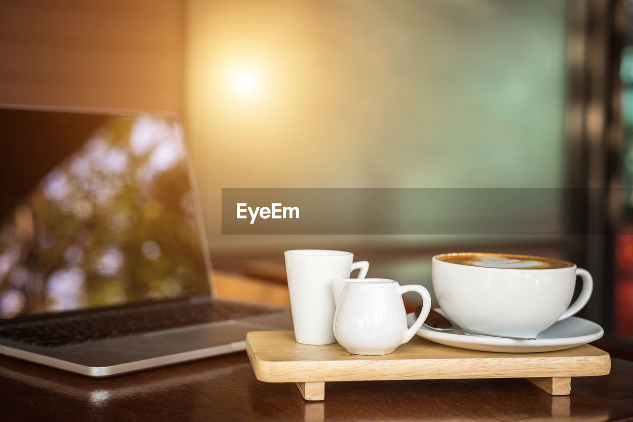 Coffee cup with laptop on wooden table
