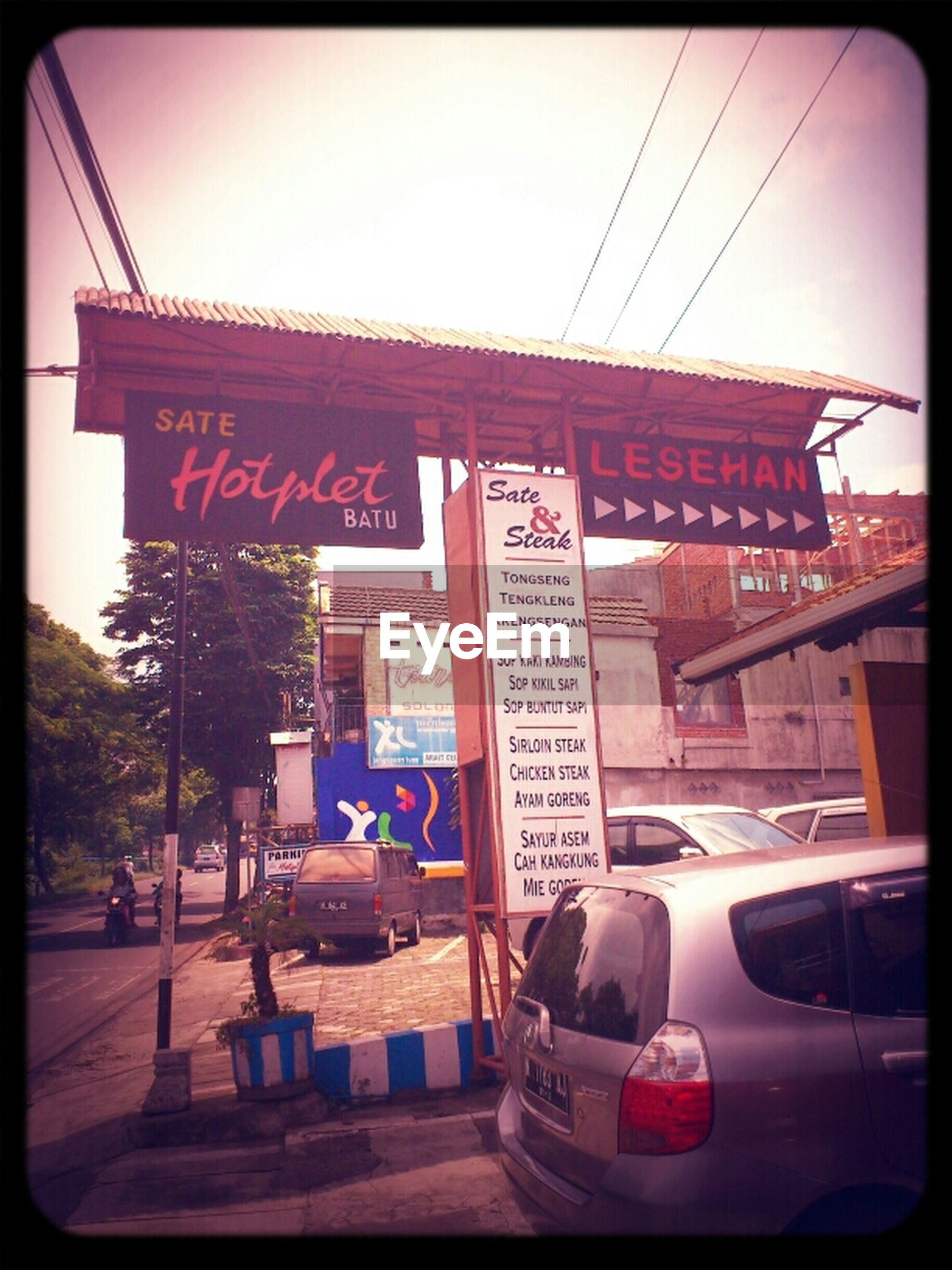 transfer print, transportation, text, auto post production filter, western script, car, architecture, communication, building exterior, mode of transport, built structure, land vehicle, street, clear sky, non-western script, day, road, sign, information sign, outdoors