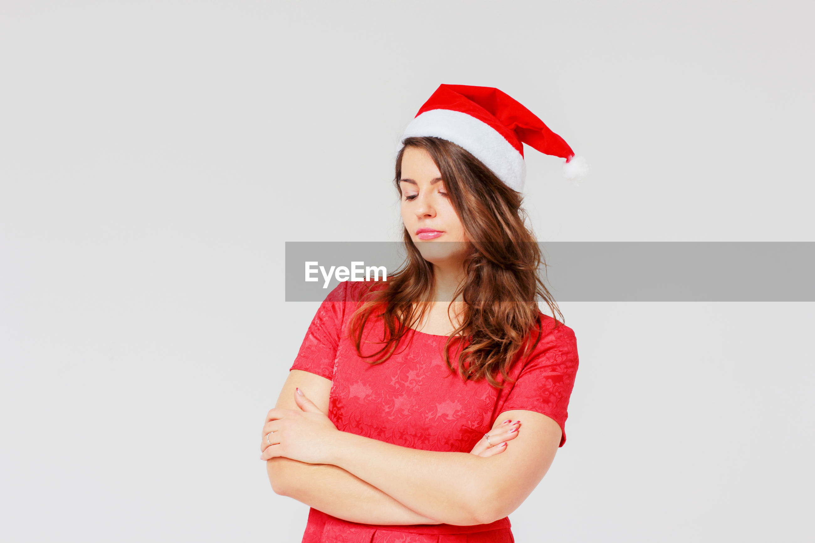 Thoughtful young woman wearing santa hat while standing arms crossed against gray background