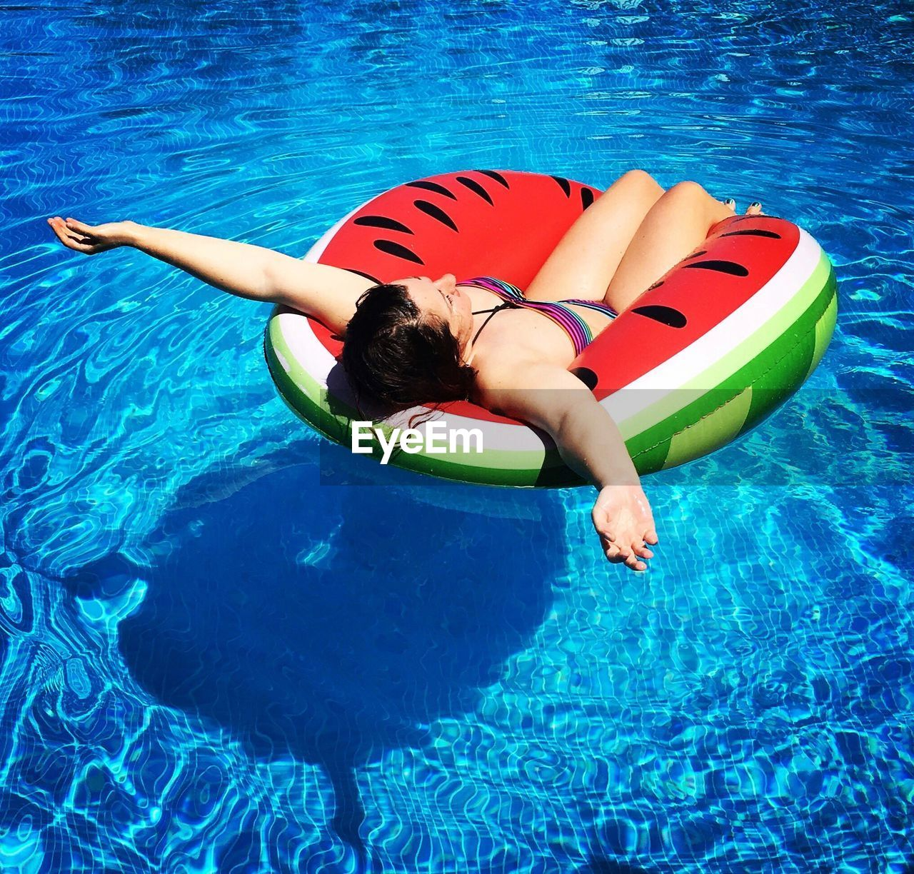 High angle view of young woman on inflatable ring in swimming pool