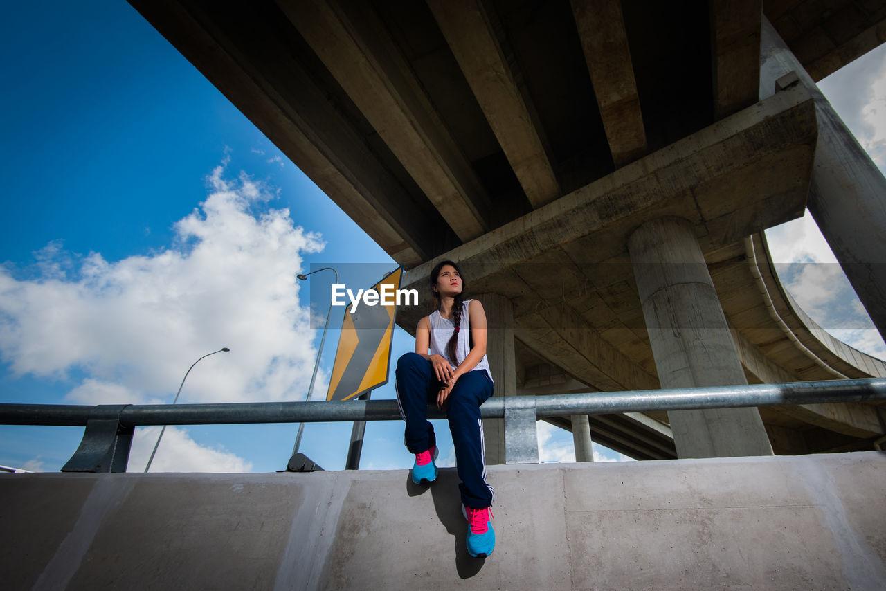 Full Length Of Woman Sitting On Railing Under Bridge