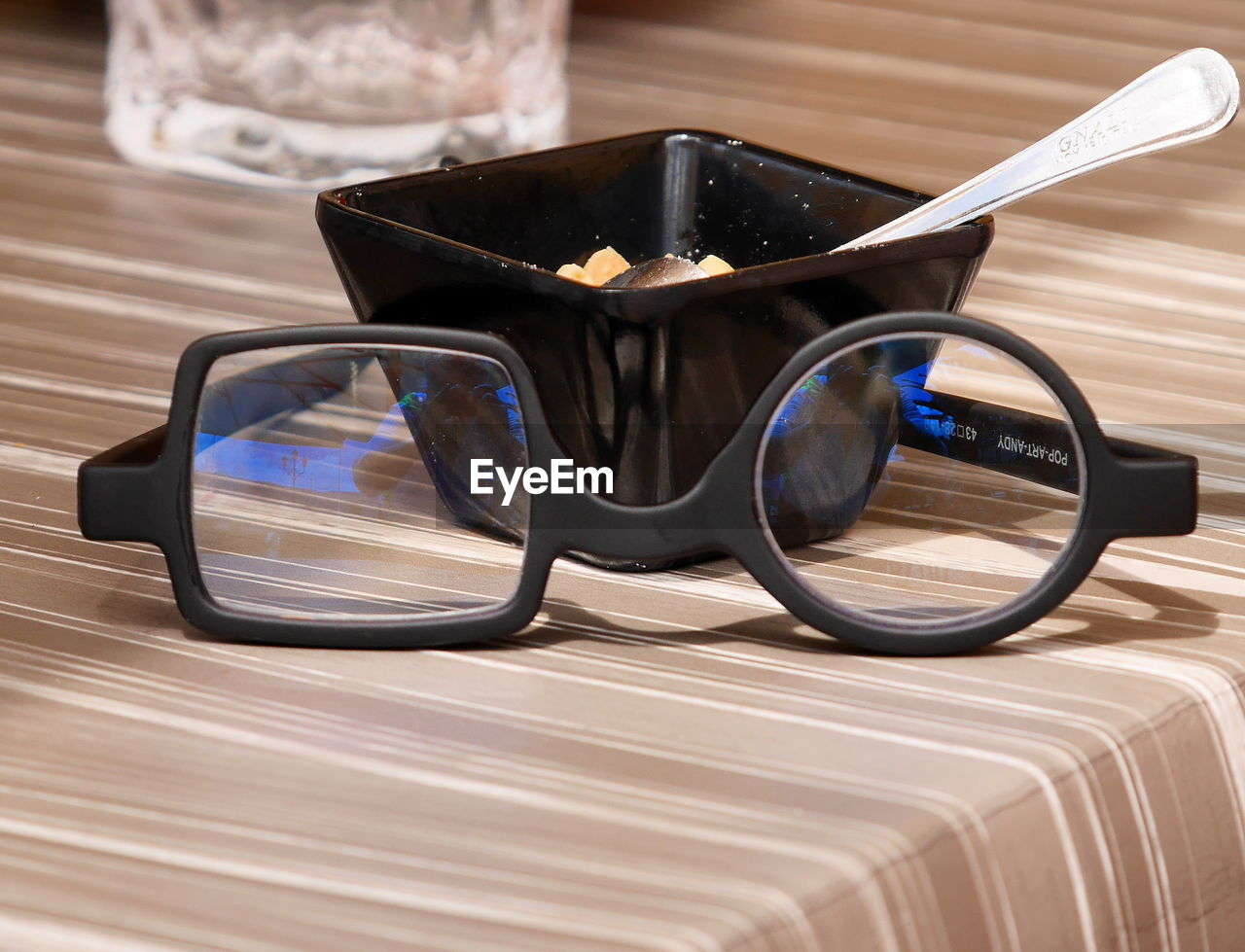 close-up, table, glasses, still life, focus on foreground, indoors, no people, fashion, sunglasses, wood - material, reflection, black color, glass - material, eyeglasses, transparent, protection, day, security, single object, personal accessory, eyewear