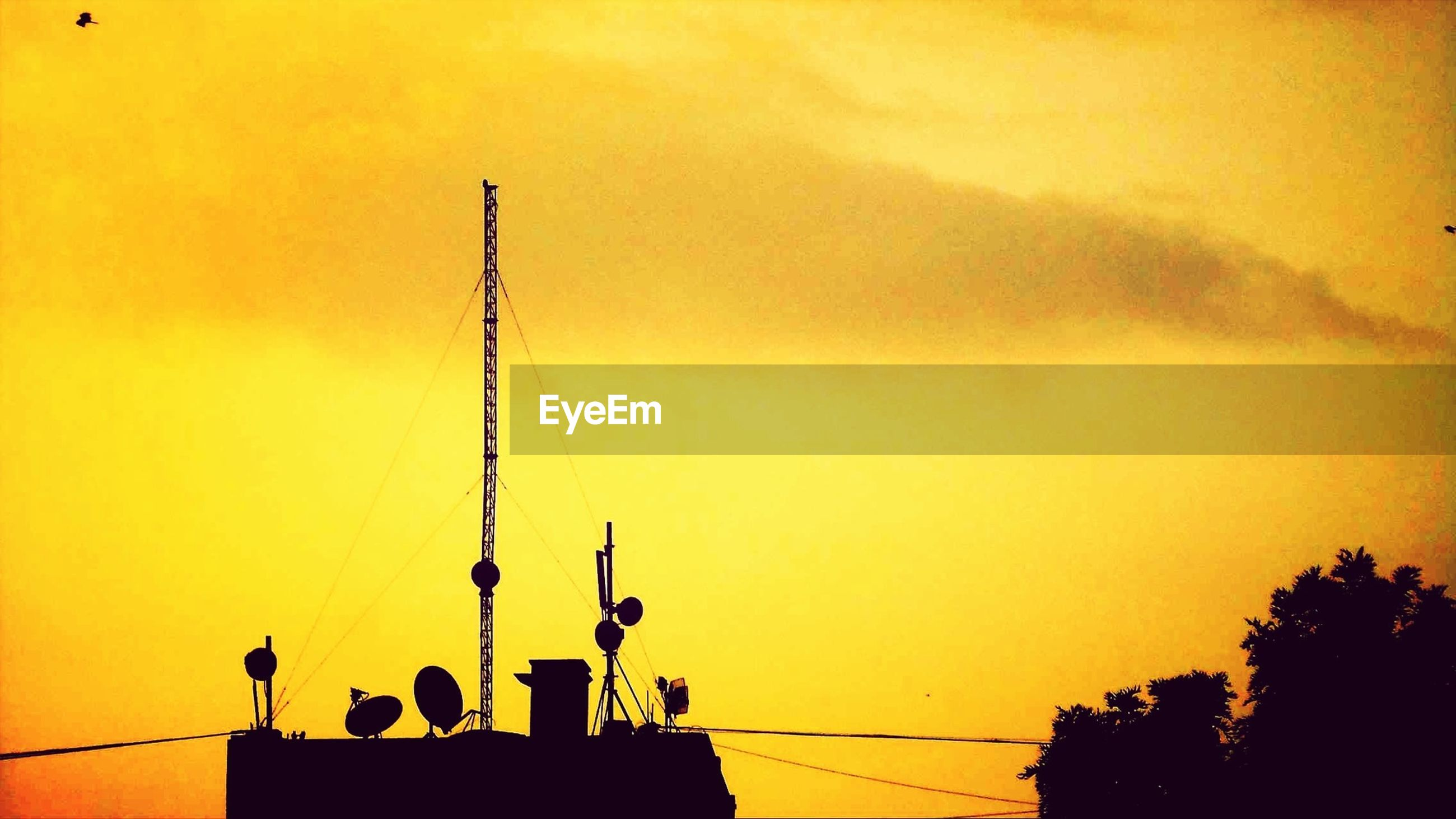 sunset, silhouette, architecture, orange color, built structure, building exterior, low angle view, sky, communications tower, street light, power line, spire, yellow, communication, copy space, outdoors, lighting equipment, high section, tower, travel destinations