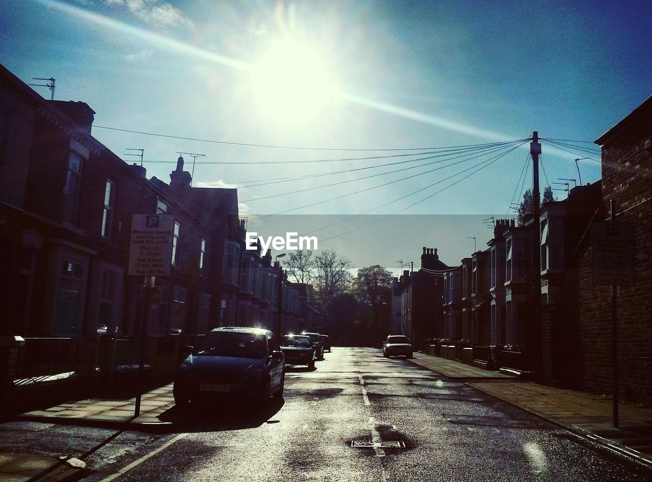 architecture, building exterior, sunlight, built structure, sun, street, road, sky, car, no people, cable, outdoors, city, day