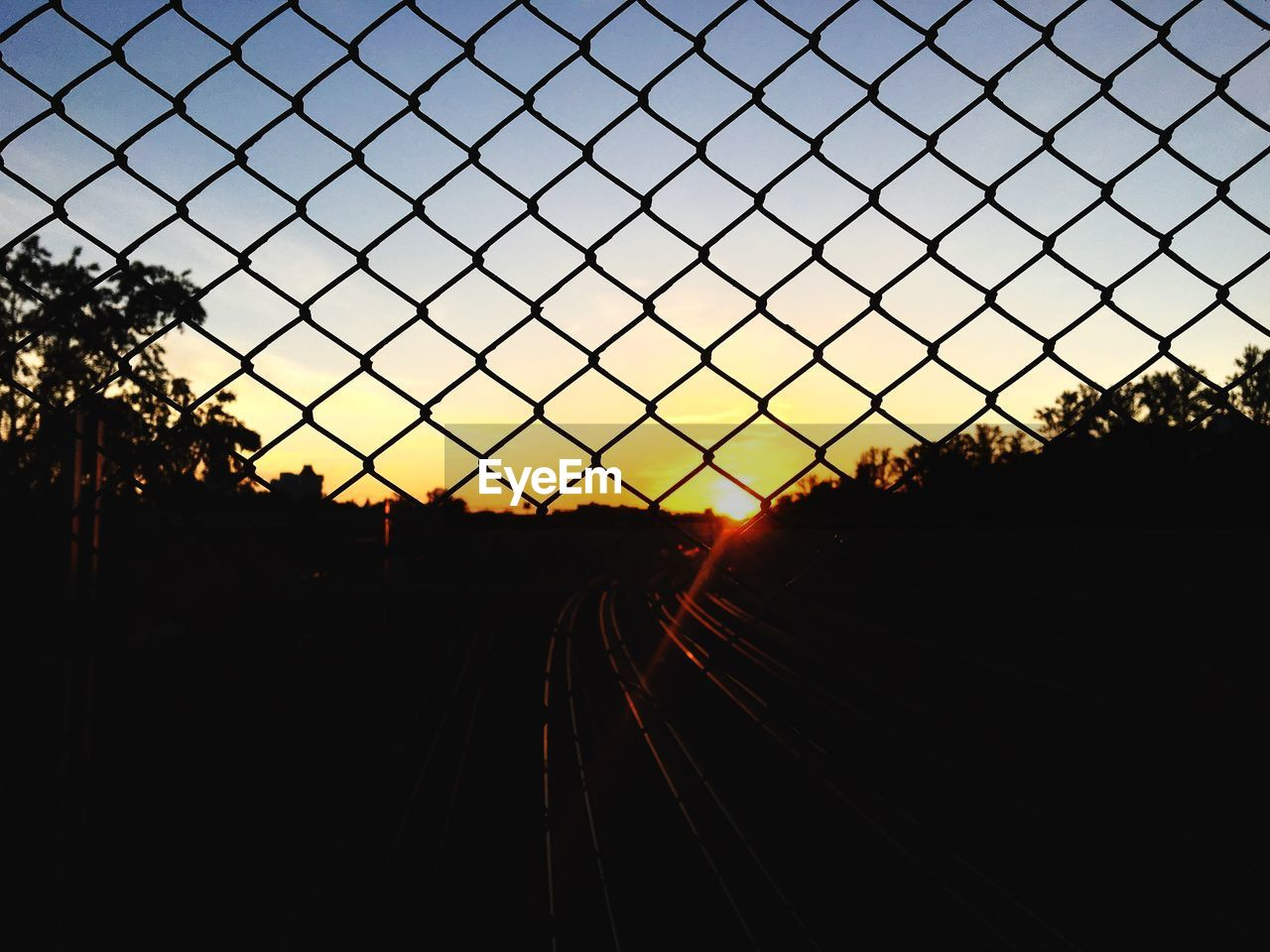 sky, sunset, silhouette, rail transportation, nature, no people, tree, track, railroad track, metal, clear sky, plant, transportation, chainlink fence, fence, outdoors, train, sunlight, security, beauty in nature