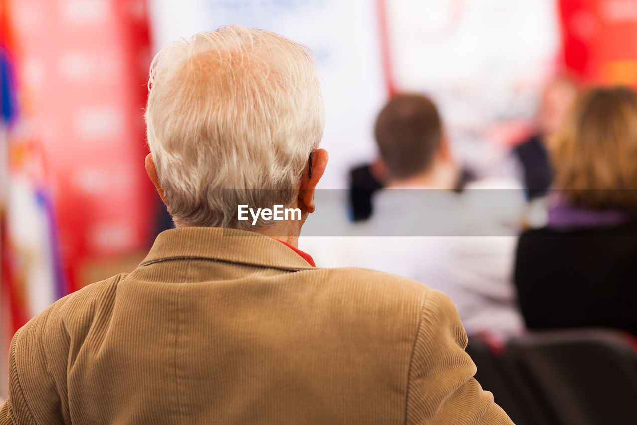 Rear View Of Senior Businessman In Seminar