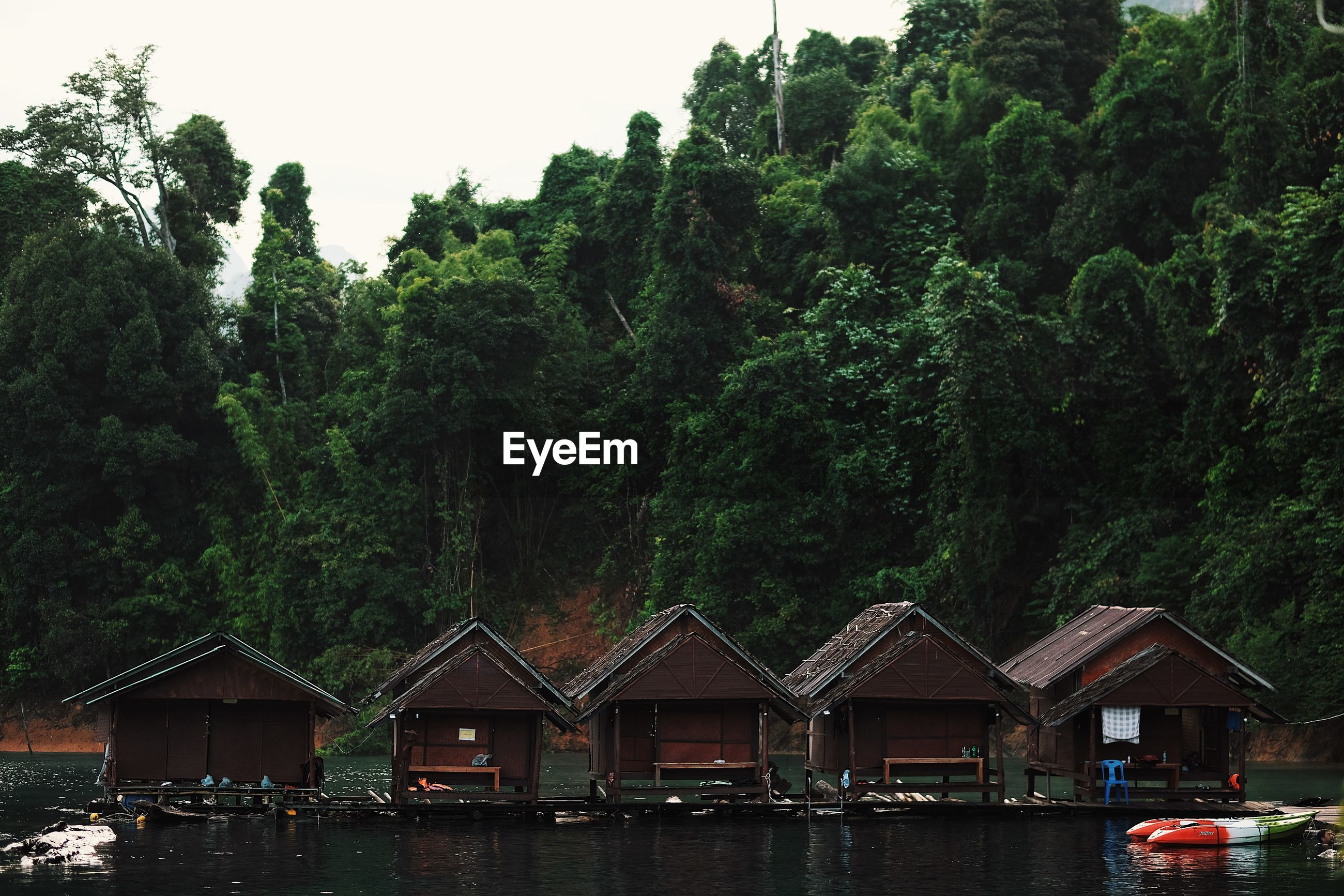 SCENIC VIEW OF LAKE BY TREES AND BUILDINGS