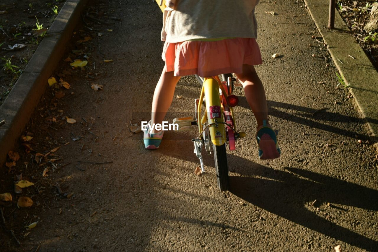 Low Section Of Girl Riding Bicycle On Footpath