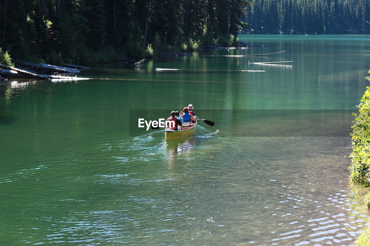 Rear View Of Four People Canoeing In Lake