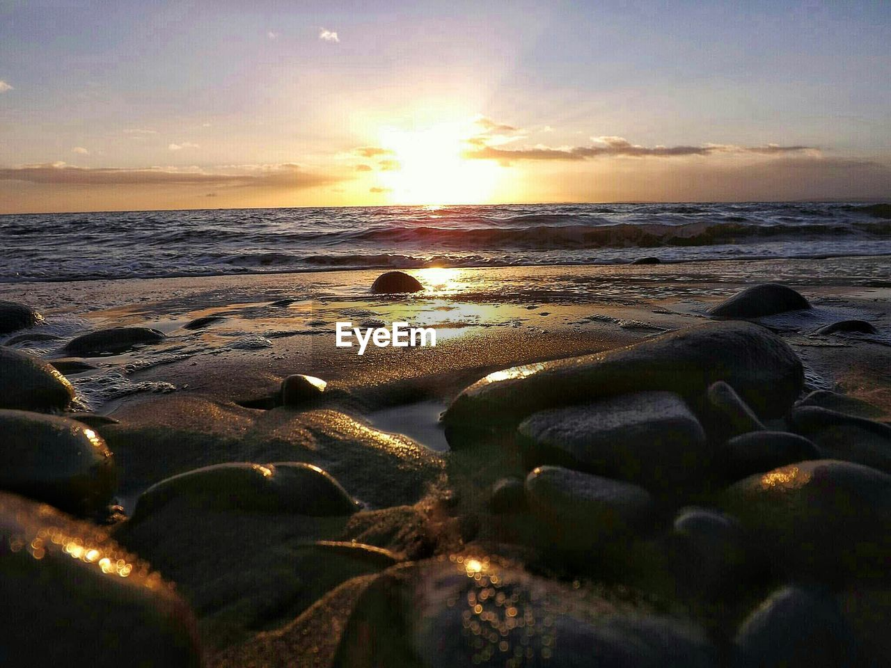 sunset, sea, beach, nature, beauty in nature, water, shore, horizon over water, scenics, tranquil scene, sky, tranquility, sun, no people, outdoors, rock - object, pebble, sand, wave, cloud - sky, pebble beach, day