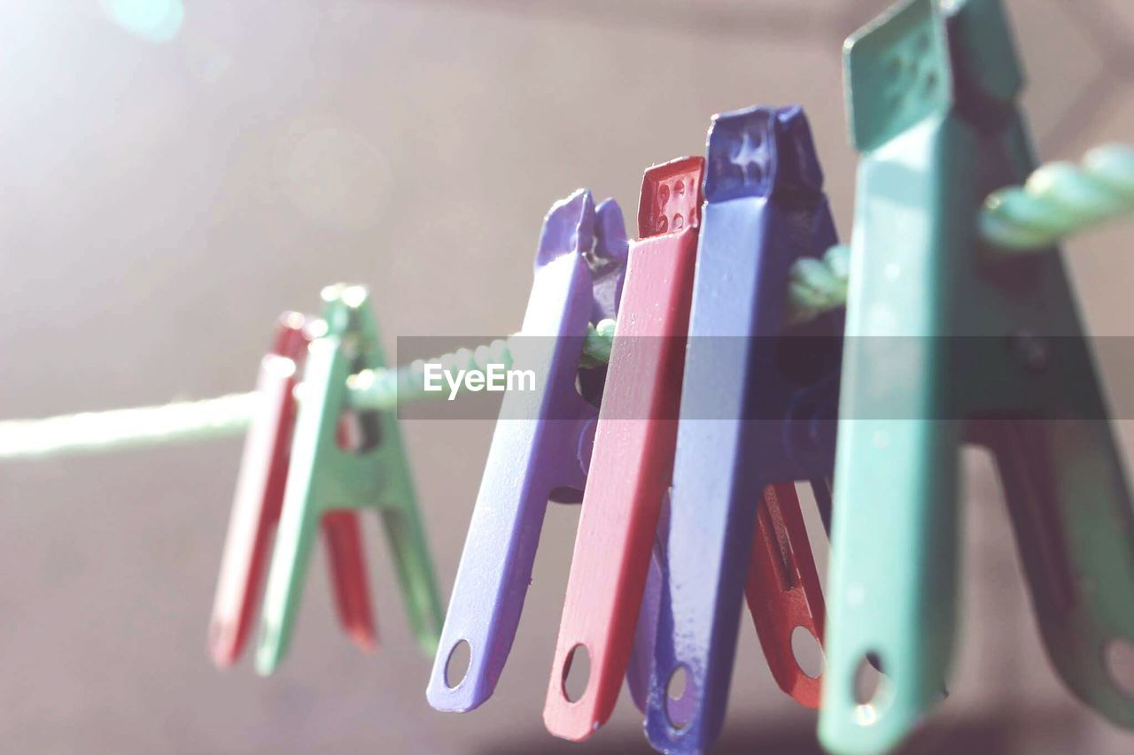 hanging, clothespin, in a row, no people, clothesline, variation, large group of objects, multi colored, day, close-up, outdoors