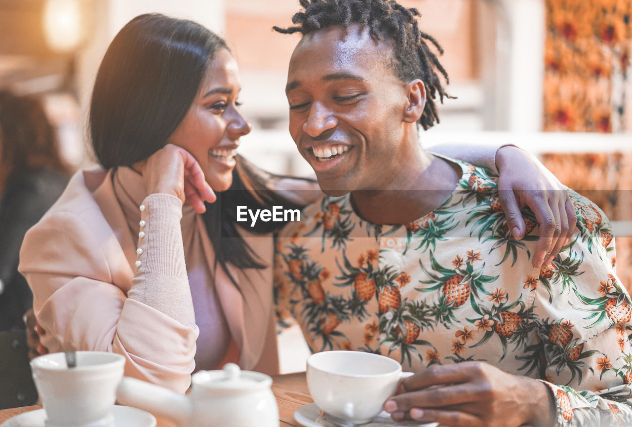 two people, real people, drink, smiling, cup, women, young adult, young women, happiness, togetherness, mug, coffee cup, sitting, leisure activity, adult, emotion, lifestyles, food and drink, coffee, couple - relationship, positive emotion, hot drink
