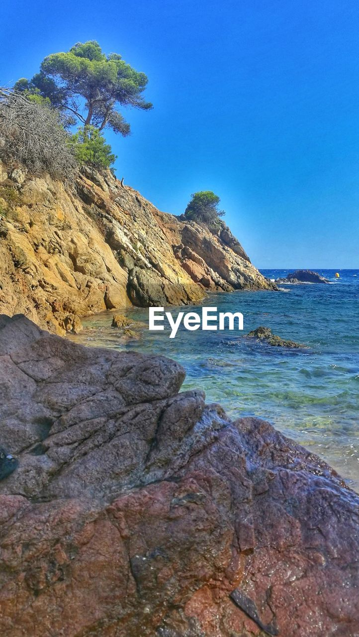 sea, blue, rock - object, nature, clear sky, scenics, beauty in nature, tranquil scene, day, tranquility, outdoors, no people, beach, horizon over water, sky, water, tree