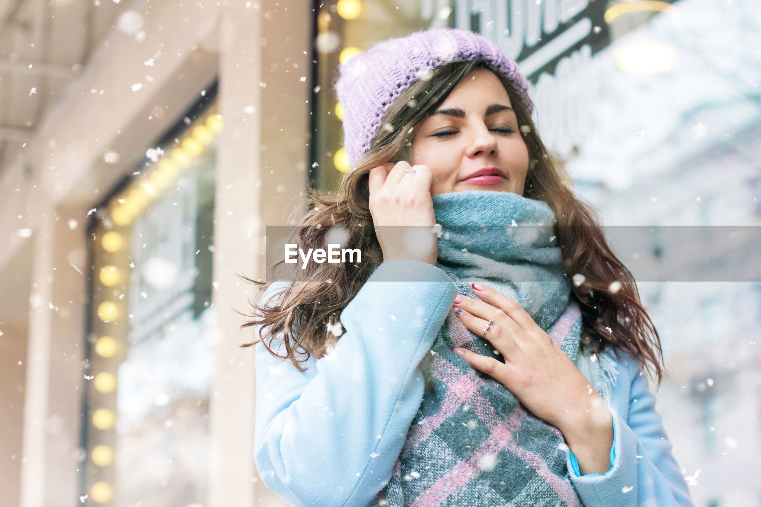 Young woman with eyes closed standing against building during snowfall