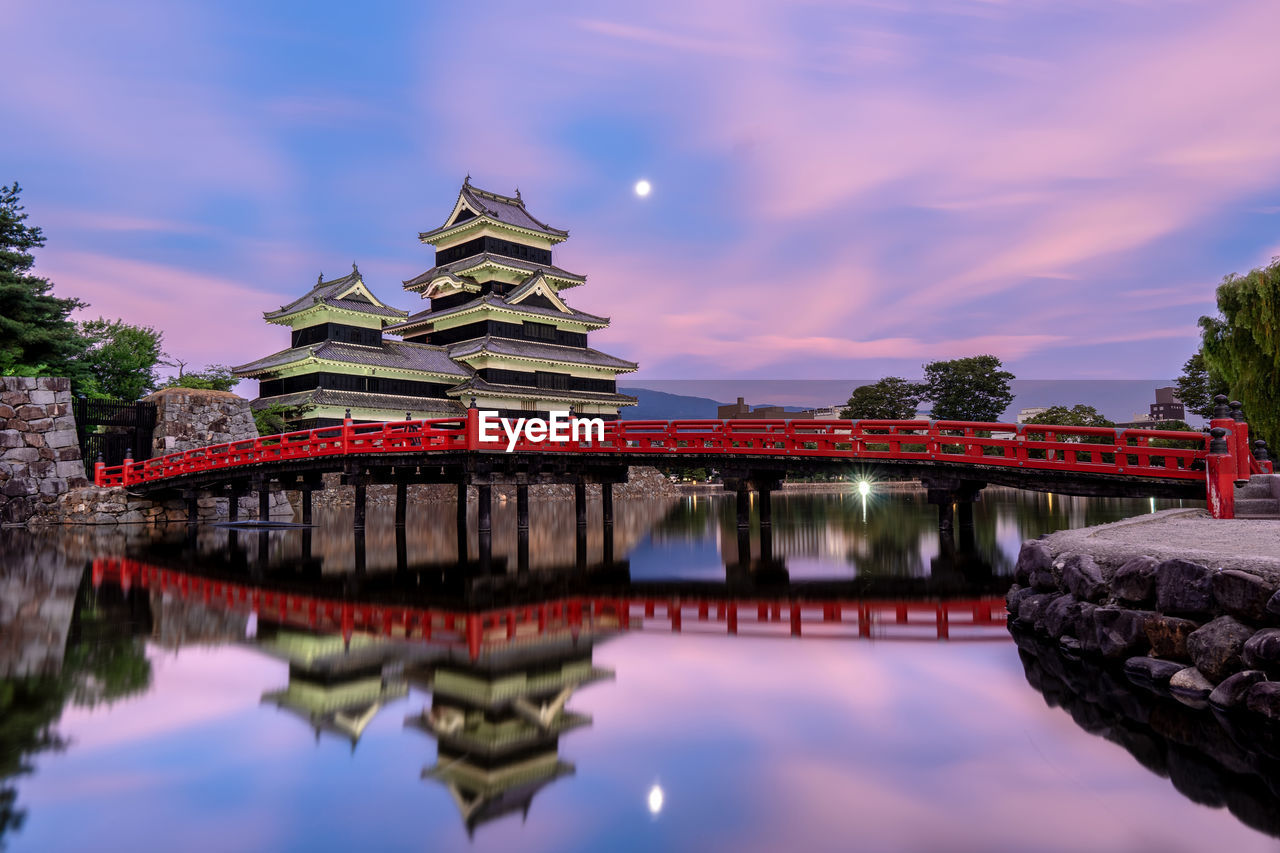 Temple by bridge and river against sky during sunset