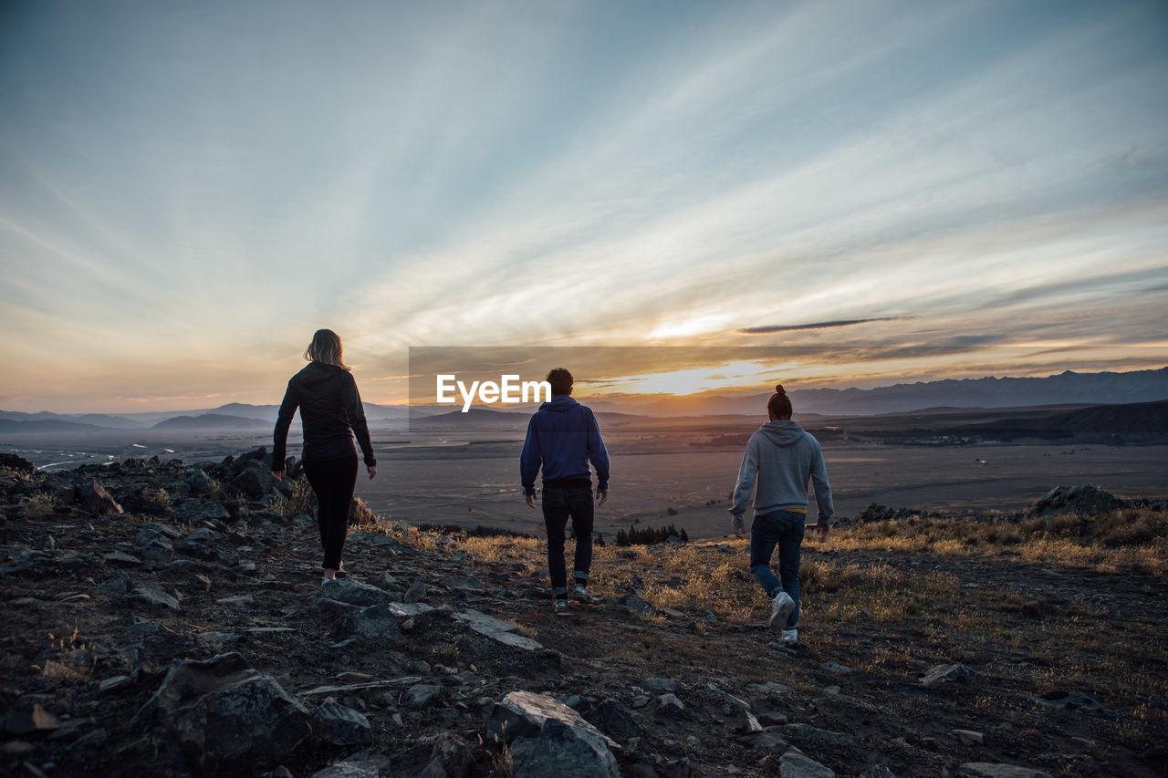 Rear View Of Friends Walking On Landscape