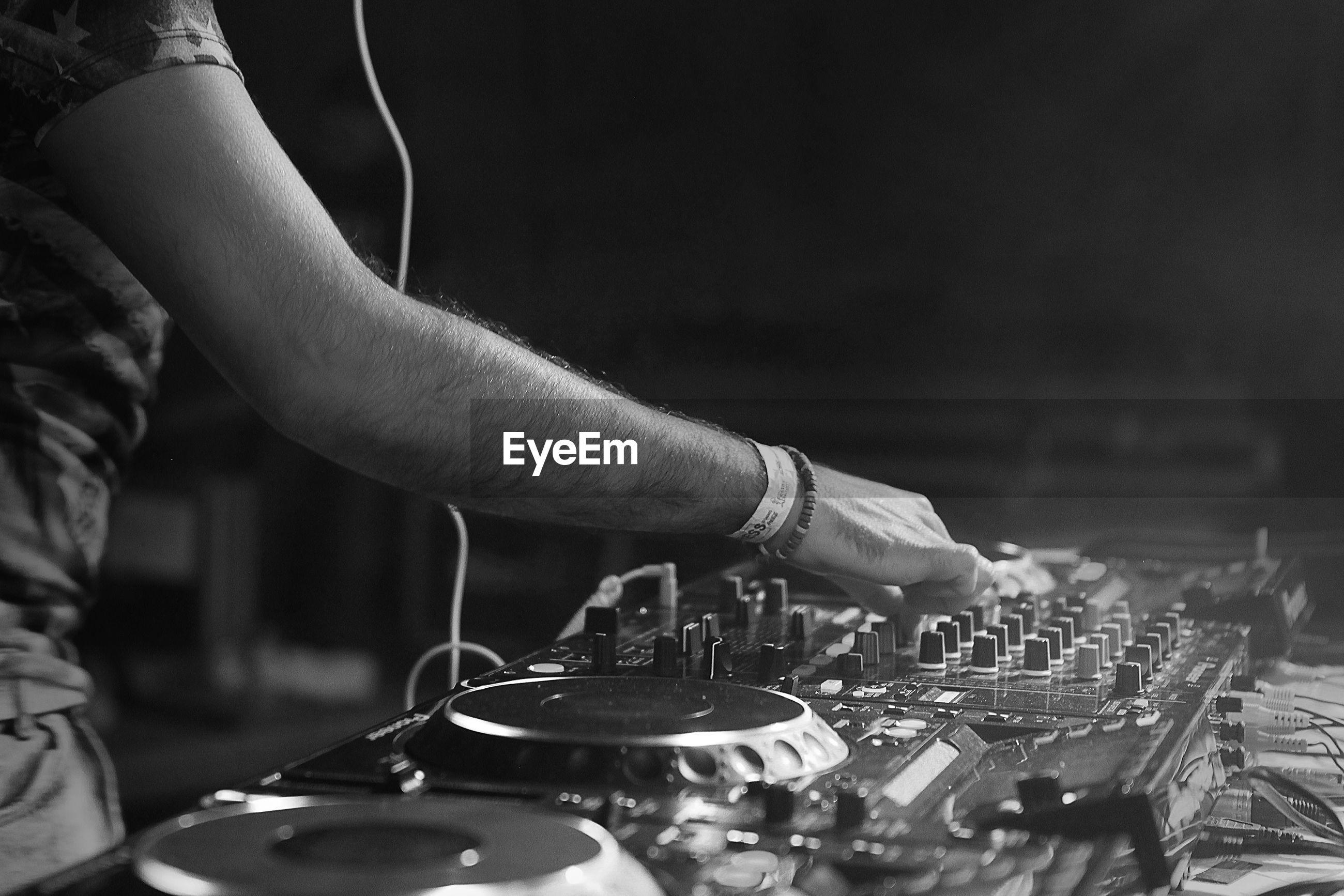 Midsection of dj adjusting sound mixer in nightclub