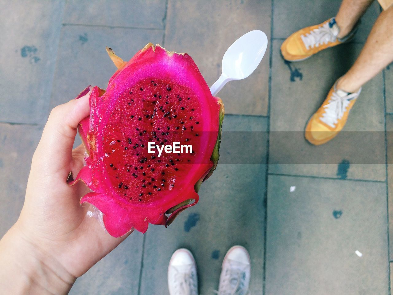 Low Section Of Friends Having Pitaya On Footpath