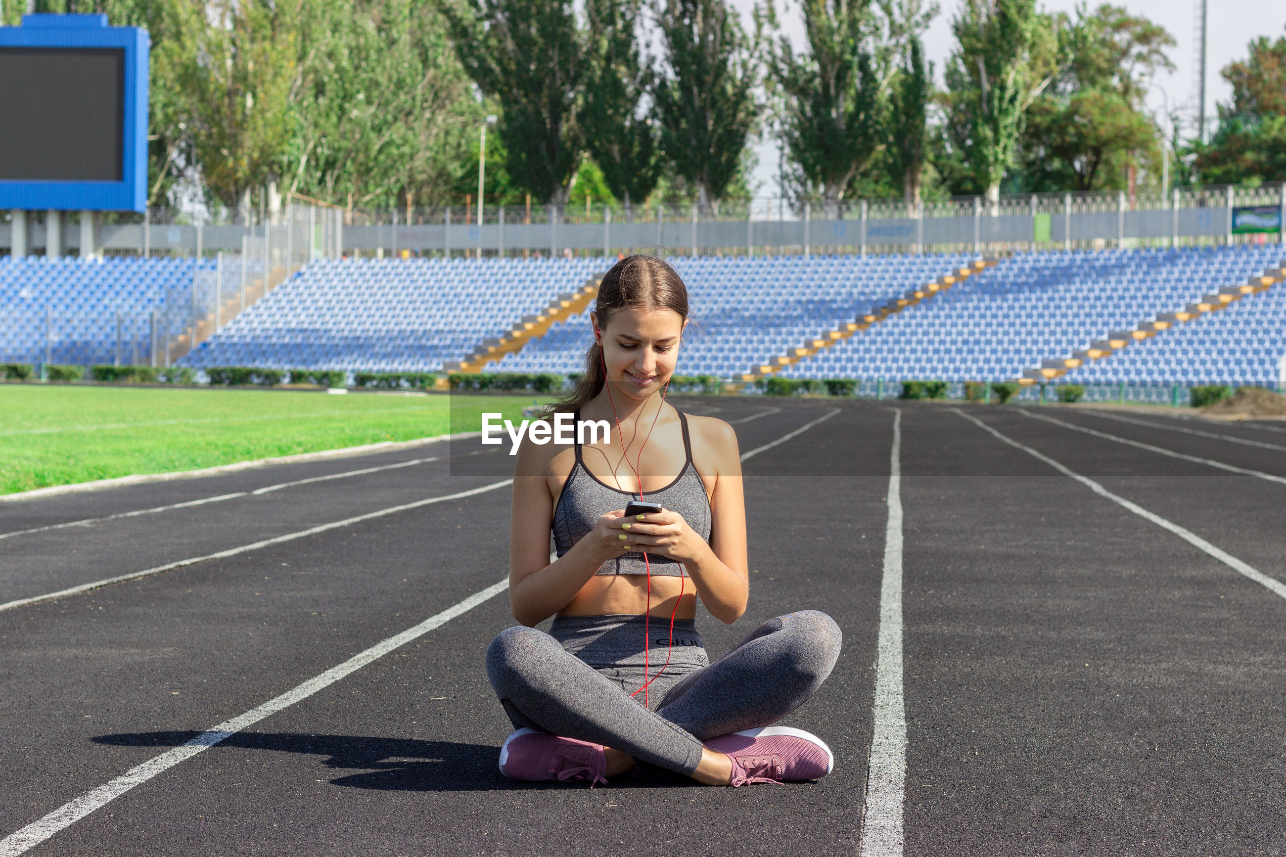 Young athlete using mobile phone while sitting on running track