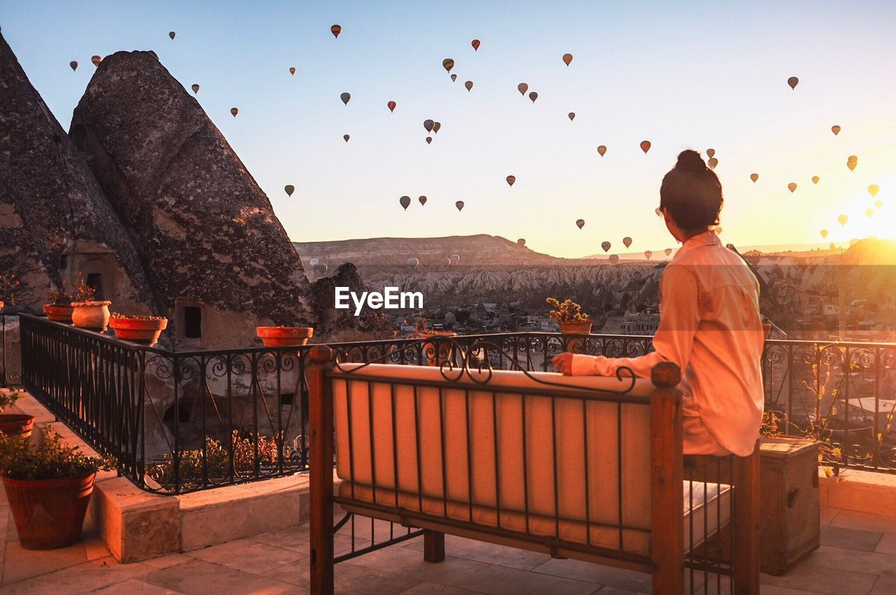 Woman Sitting In Balcony While Looking At Hot Air Balloons During Sunset