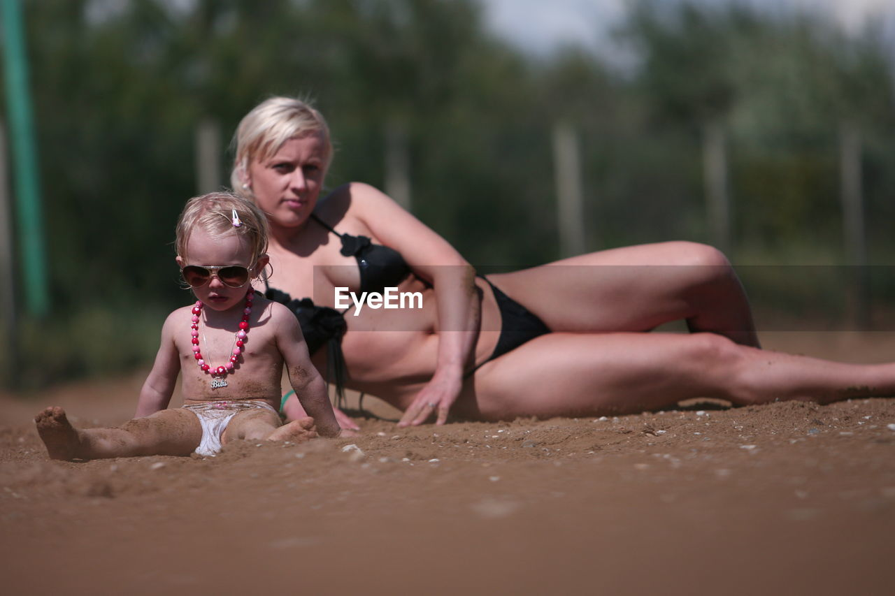 real people, outdoors, childhood, selective focus, day, mother, lifestyles, family, leisure activity, girls, shirtless, boys, sand, togetherness, two people, vacations, full length, young women, water, sitting, young adult, people