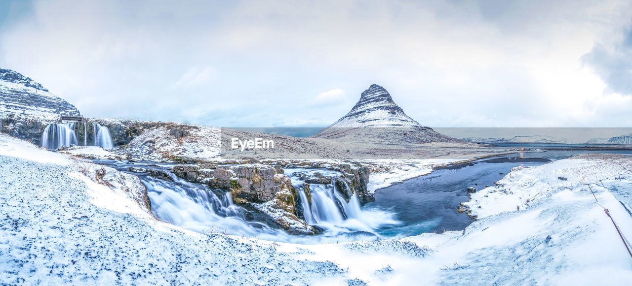 Scenic view of snowcapped mountain and waterfall against sky