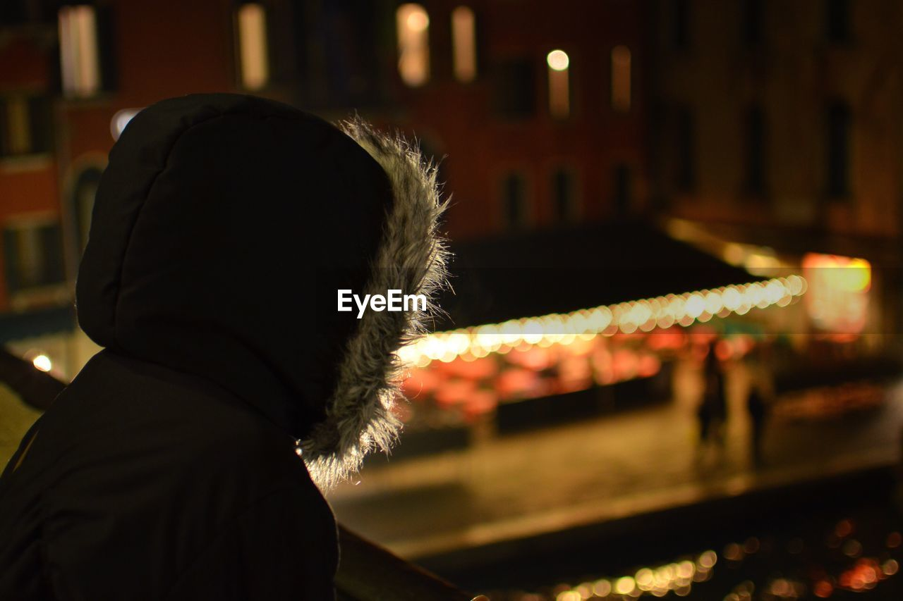 Side view of person on hooded jacket looking at illuminated city
