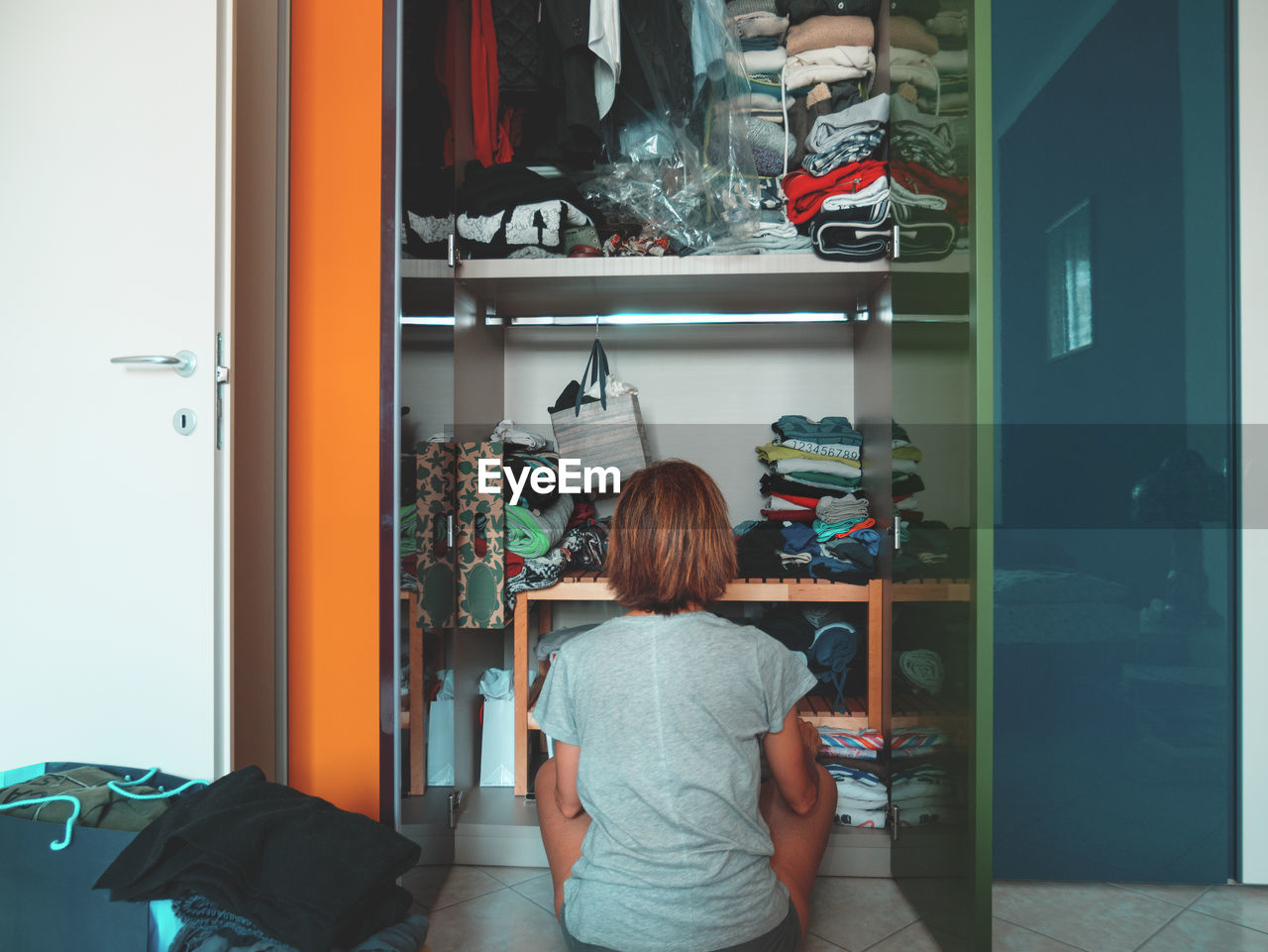 Rear View Of Woman Looking In Cabinet While Sitting At Home