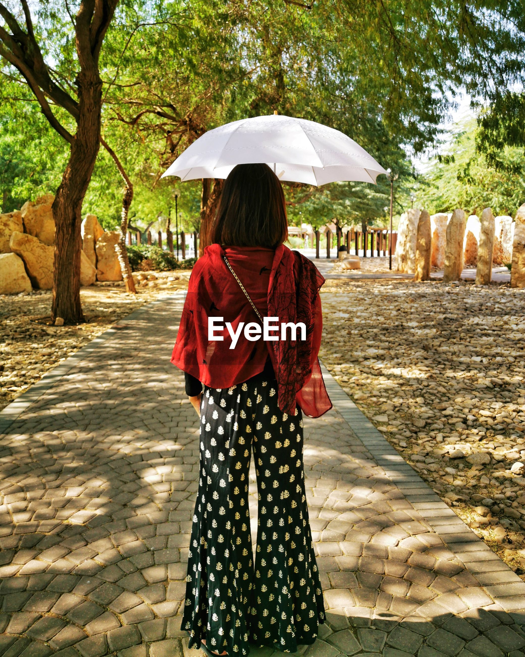 Rear view of woman holding umbrella while standing on footpath