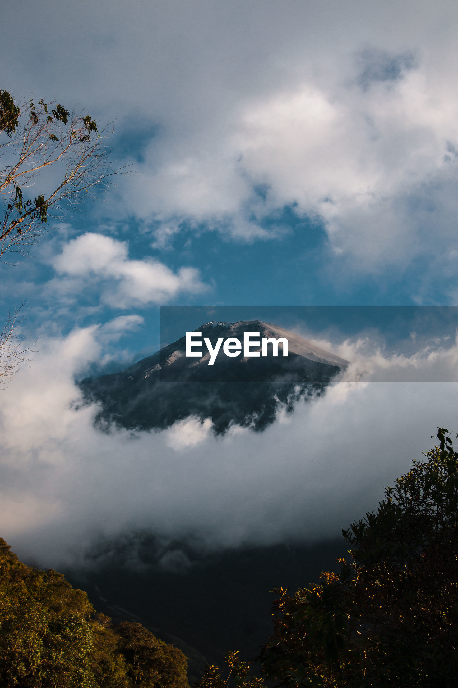 Scenic view of mountain through cloudy sky