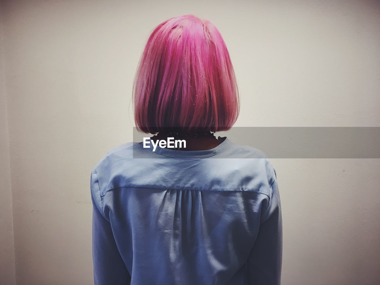 Rear view of woman with pink hair standing against wall at home