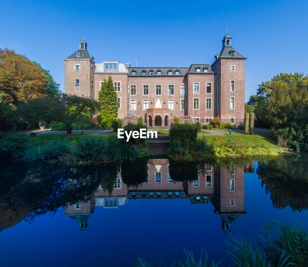 building exterior, built structure, architecture, water, reflection, sky, plant, nature, building, tree, the past, blue, waterfront, travel destinations, lake, mansion, history, no people, tourism, luxury