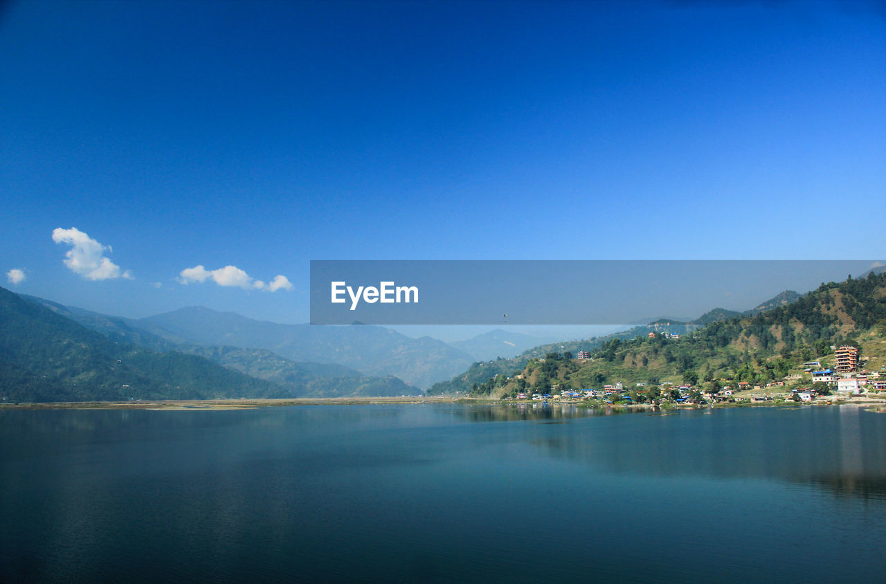 mountain, water, sky, scenics - nature, beauty in nature, copy space, blue, waterfront, mountain range, lake, tranquility, no people, nature, tranquil scene, clear sky, reflection, idyllic, building exterior, architecture, outdoors