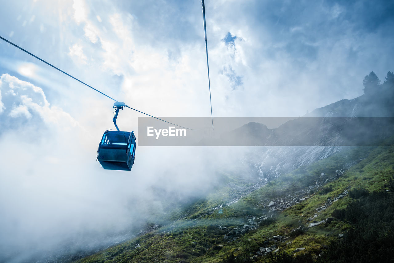 Low Angle View Of Overhead Cable Car At Mountains Against Cloudy Sky