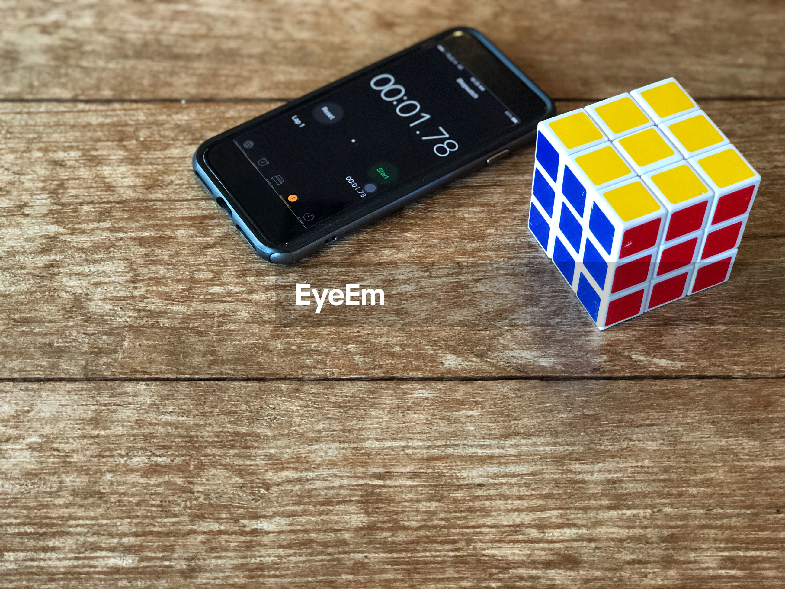 High angle view of puzzle cube with smart phone displaying stopwatch on wooden table