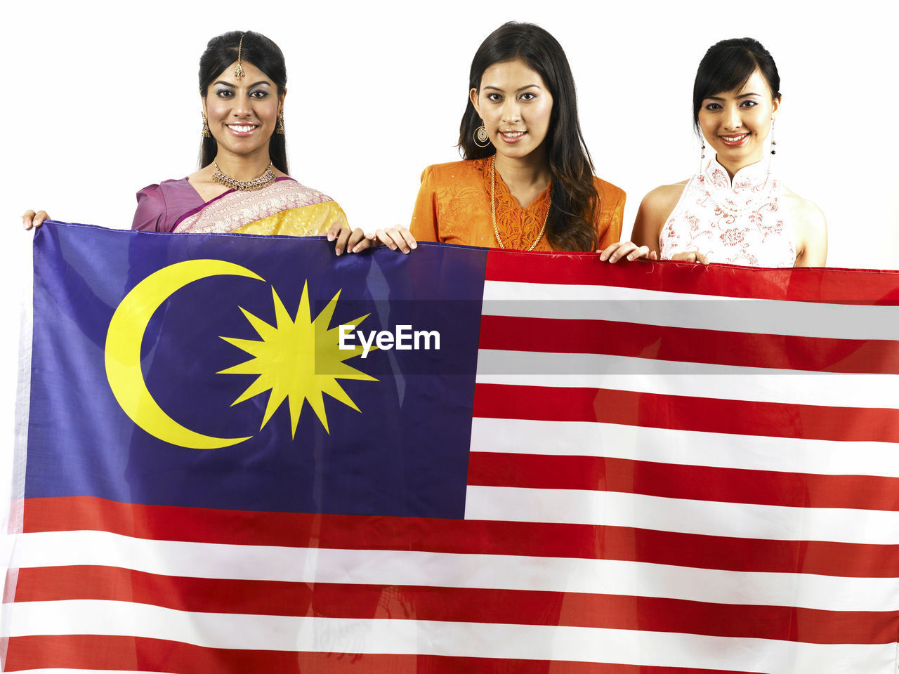 Portrait Of Happy Young Friends Holding Malaysian Flag Against White Background