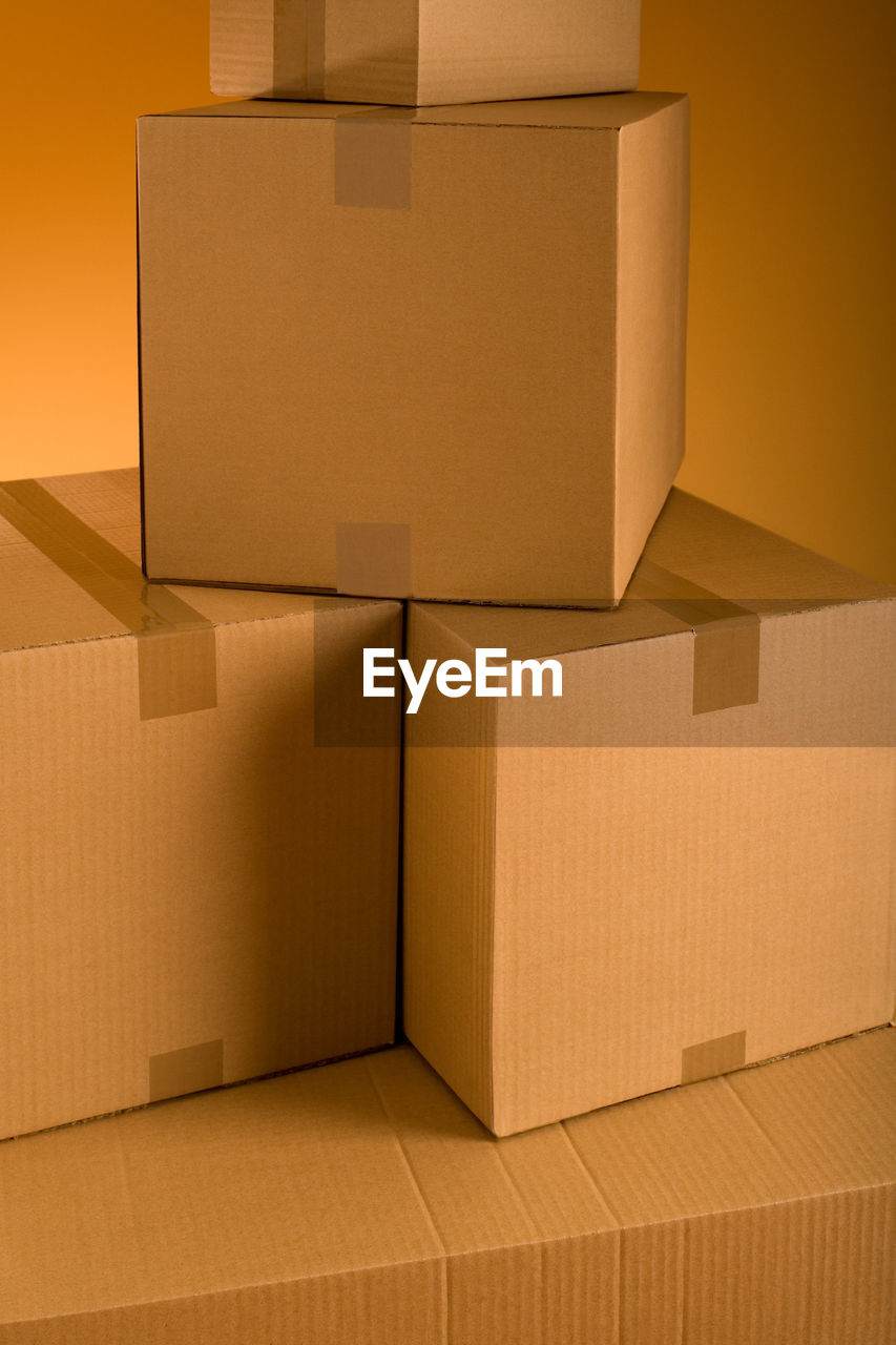 Stack of cardboard boxes against colored background