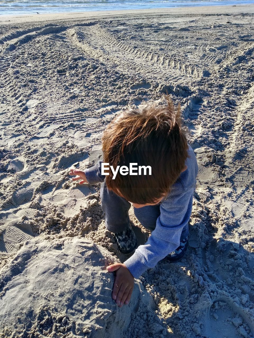 High angle view of cute boy making sandcastle on beach