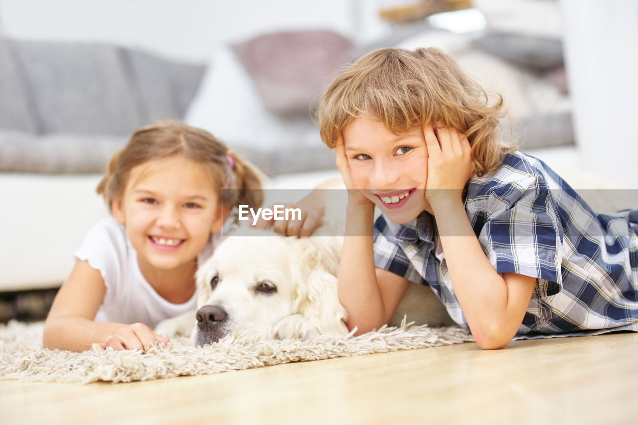 Portrait of smiling siblings with dog lying at home
