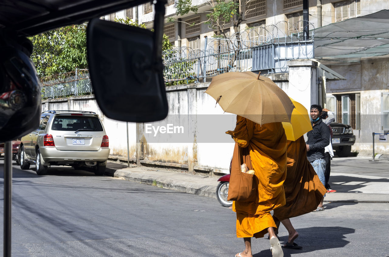 real people, walking, rear view, men, street, car, mode of transport, transportation, women, day, outdoors, road, land vehicle, city, built structure, full length, yellow, two people, lifestyles, architecture, people