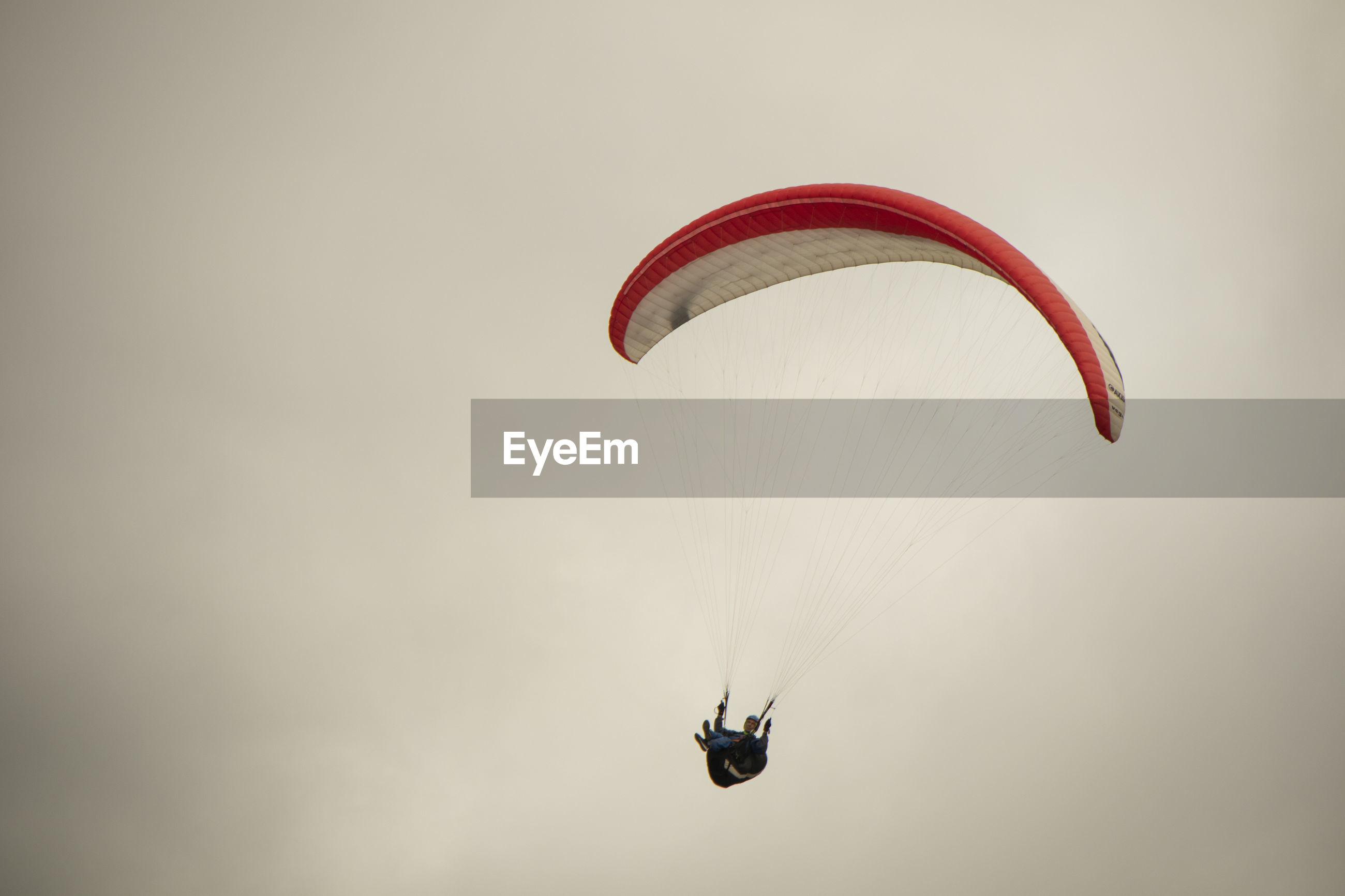LOW ANGLE VIEW OF PERSON PARAGLIDING AGAINST SKY AGAINST CLEAR BACKGROUND