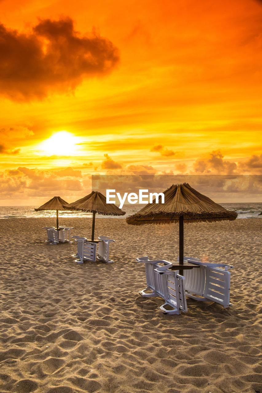 sky, land, sunset, sand, beach, sea, scenics - nature, water, cloud - sky, beauty in nature, tranquil scene, tranquility, nature, orange color, chair, parasol, idyllic, absence, horizon, horizon over water, no people, outdoors, outdoor chair