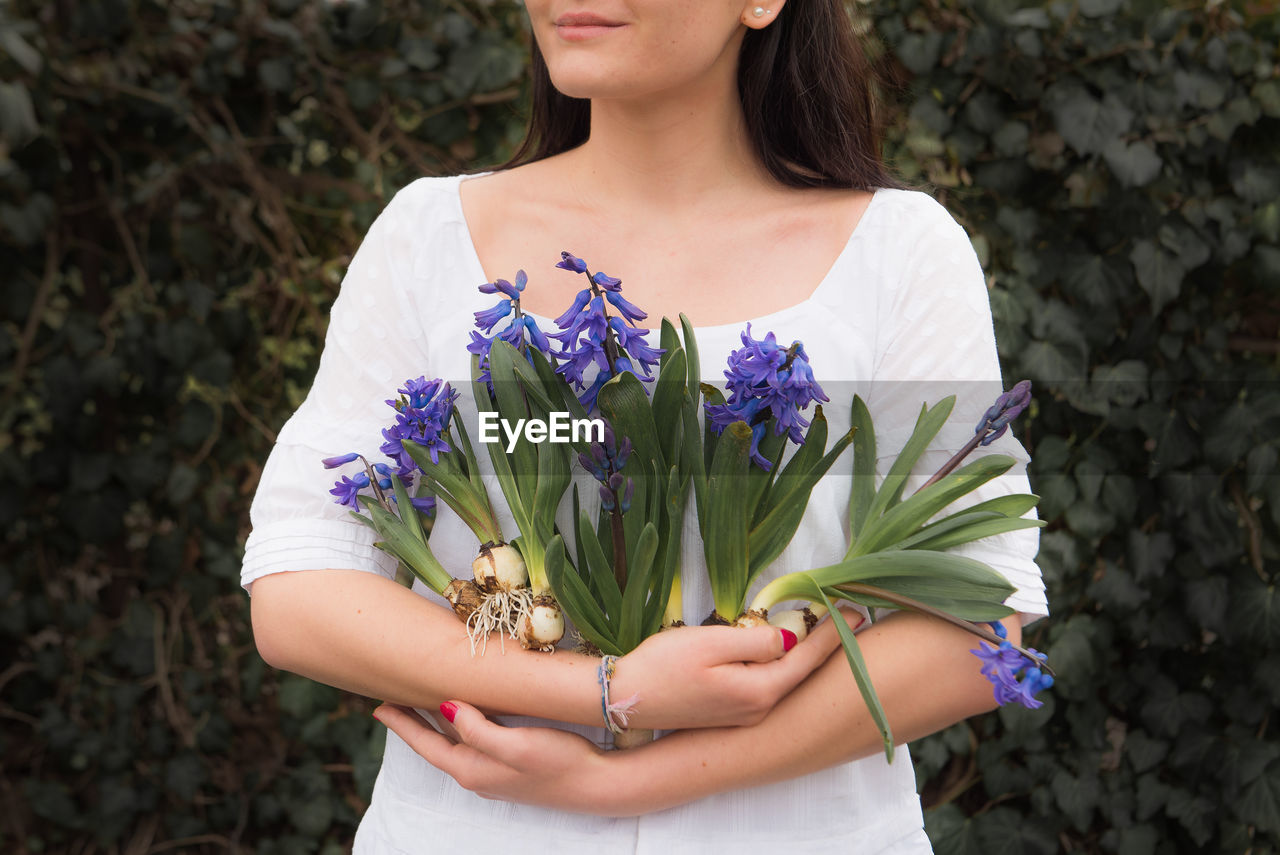 Midsection of woman holding purple flower